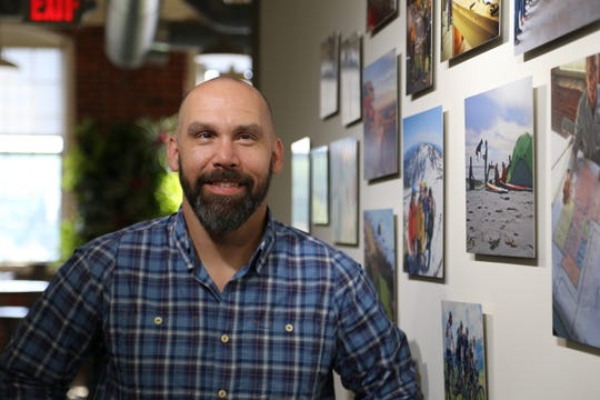 NEMO Equipment CEO Cam Brensinger stands next to a wall of photos at the company's Dover, N.H. headquarters. The photos depict some of the company's pivotal moments.