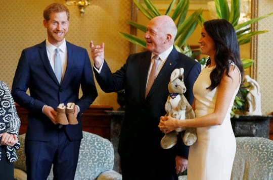 Meghan, right, Duchess of Sussex, reacts as she and Prince Harry, left, receive gifts from Australia's Governor General Sir Peter Cosgrove in Sydney, Australia.