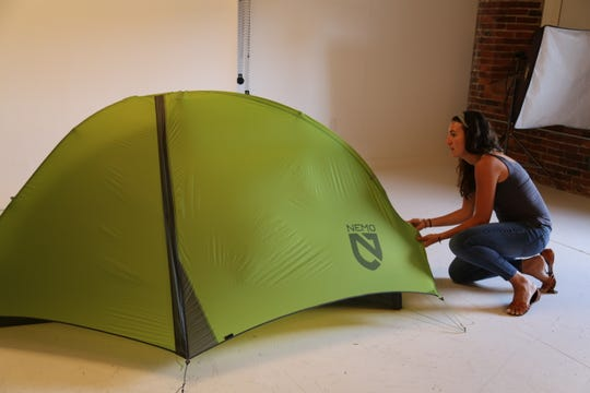 NEMO Equipment's graphic designer Sam Strong, right, prepares a tent for a promotional photo in the company's on-site studio in Dover, N.H.