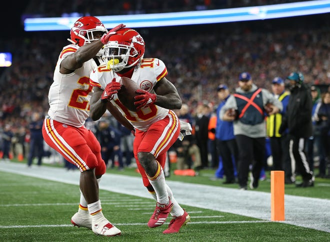 Tyreek Hill of the Kansas City Chiefs celebrates a touchdown pass with Kareem Hunt #27 of the Kansas City Chiefs against the  New England Patriots in the fourth quarter at Gillette Stadium on October 14, 2018 in Foxborough, Massachusetts.