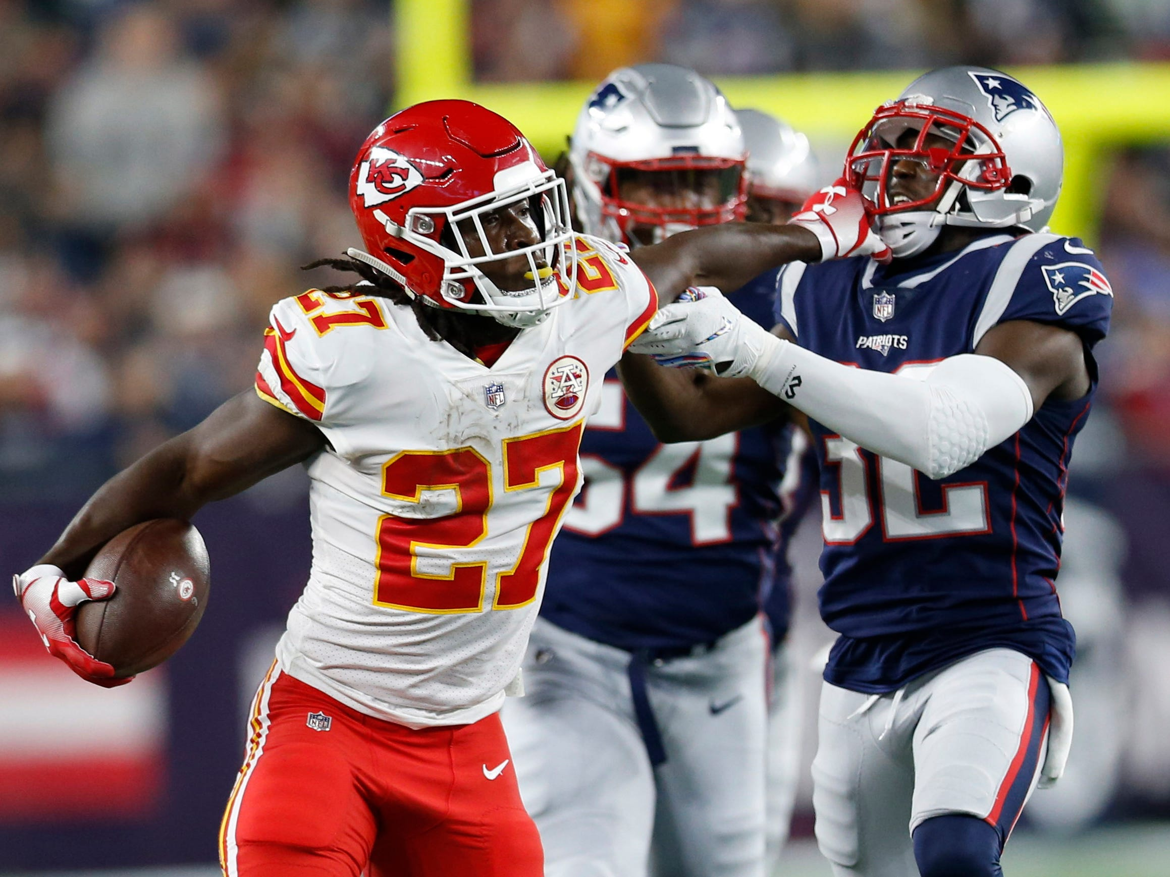 Kansas City Chiefs running back Kareem Hunt runs with the ball and tries to fend off the New England Patriots' Devin McCourty (32) during the second quarter at Gillette Stadium.