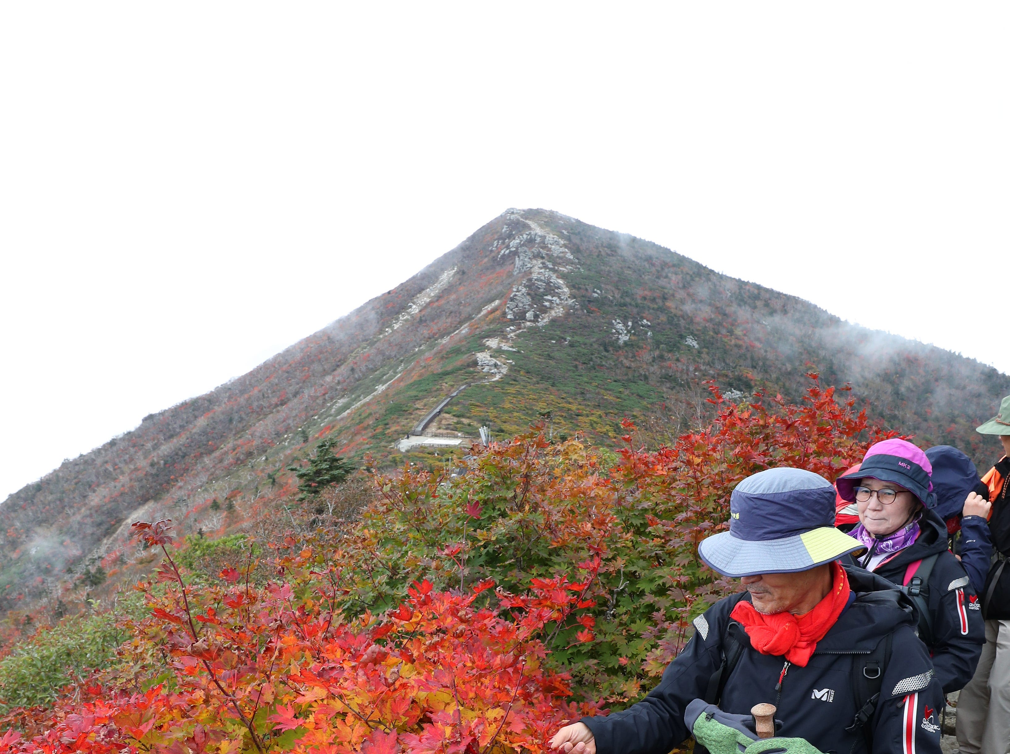 Mountaineers walk along a trail near Jungcheong Shelter on Mount Seorak in Yangyang, Gangwon, South Korea on Sept. 28, 2018, as trees on the mountain turn autumn colors of red and yellow. A definition by the Korea Meteorological Administration says that the start of the changing of the leaves is pronounced when 20 percent of the mountain's trees from its peak are tinged.