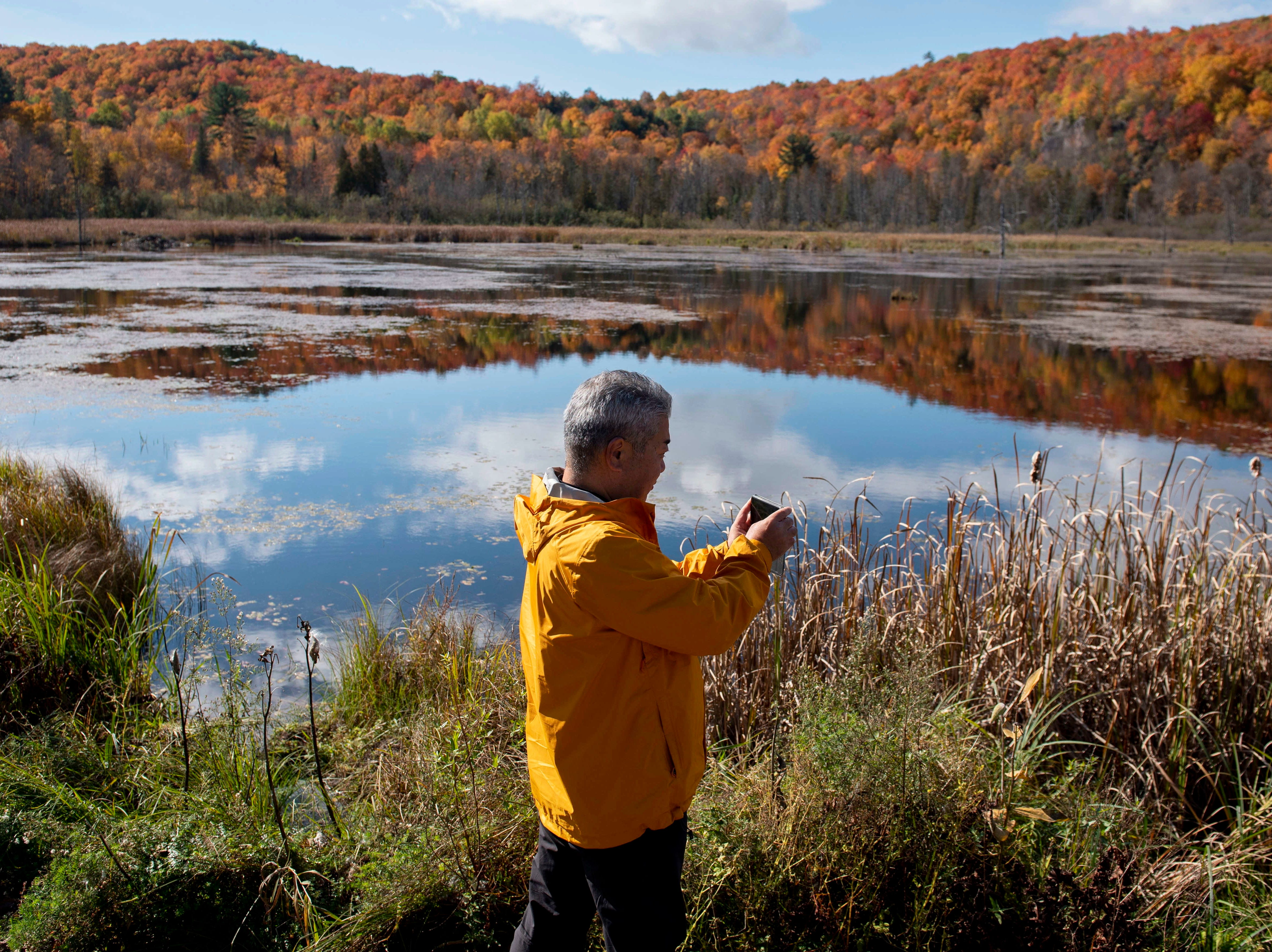 Seishi Tokuoka takes photos of the fall colors in Gatineau Park in Chelsea, Quebec, on Sunday, Oct. 14, 2018.