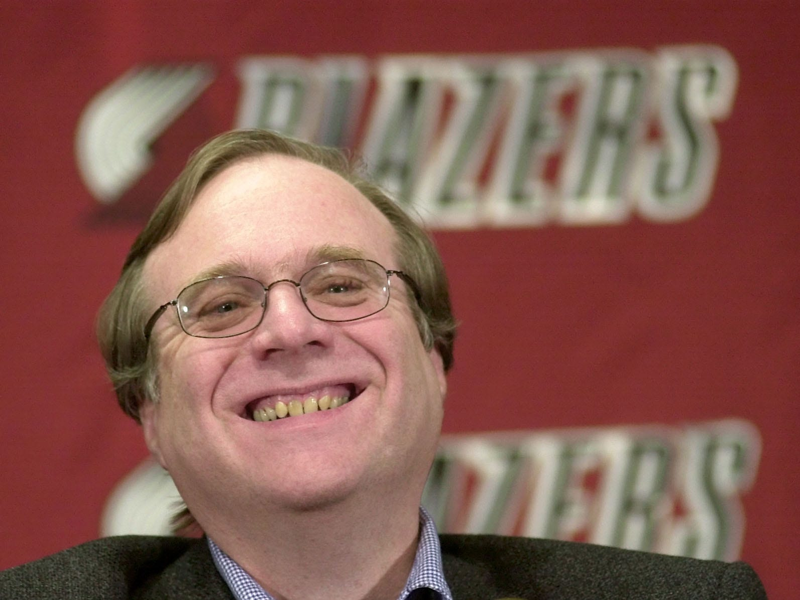 Portland Trail Blazers owner Paul Allen smiles as he talks at the Rose Garden arena during halftime of the Blazers game against the Utah Jazz in Portland, Ore., Tuesday, Feb. 10, 2004.