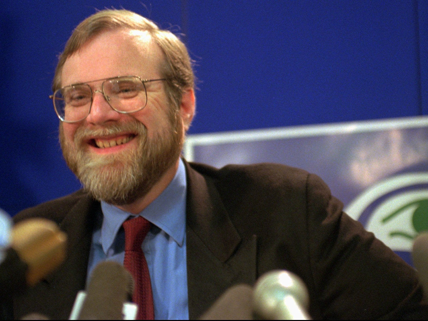 With the eye of the team logo peering over his shoulder, Microsoft co-founder Paul Allen laughs during a news conference at Seattle Seahawk headquarters Tuesday, April 23, 1996 in Kirkland, Wash. Allen says he purchased an option to buy the team to keep the Seahawks in Seattle.