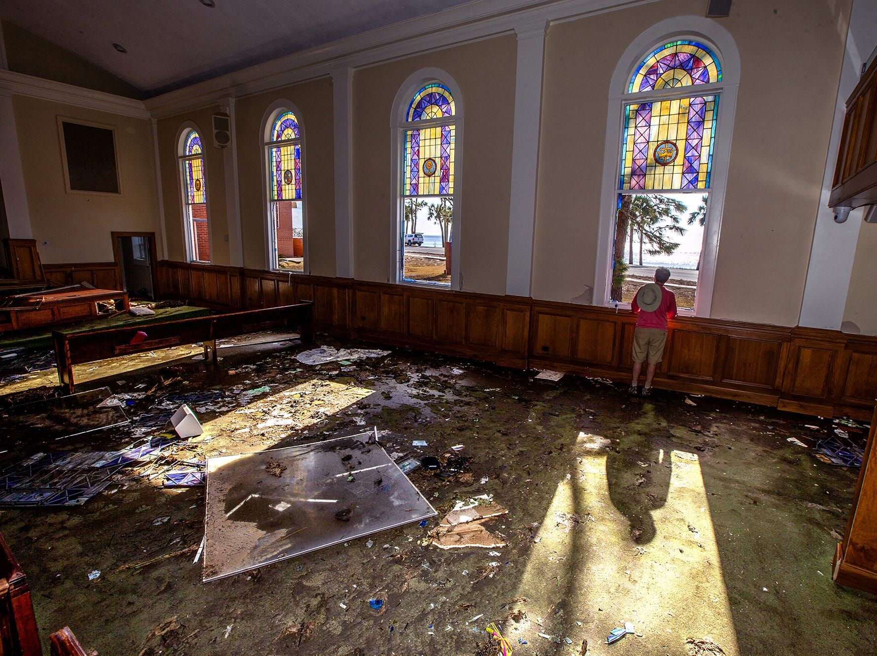 Pastor Geoffrey Lentz looks out at St Joe Bay from his sanctuary of the First United Methodist Church after it was gutted by the storm surge from Hurricane Michael on Oct. 14, 2018 in Port Saint Joe, Fla.  The surge took out the bottom half all the stain glass windows.