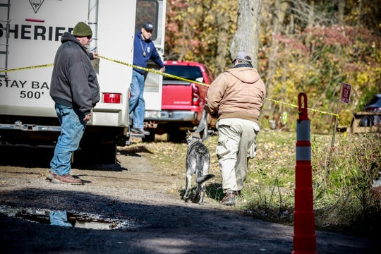 Investigators use a canine Tuesday to help search the grounds near the Closs home in Barron.