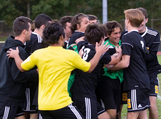 Southern's Braden Dugan is mobbed by team mates after Southern wins on penalty kicks. Southern Regional Boys Soccer beats Howell on Penalty Kicks in SCT tournament game in Stafford, NJ on October 16, 2018.