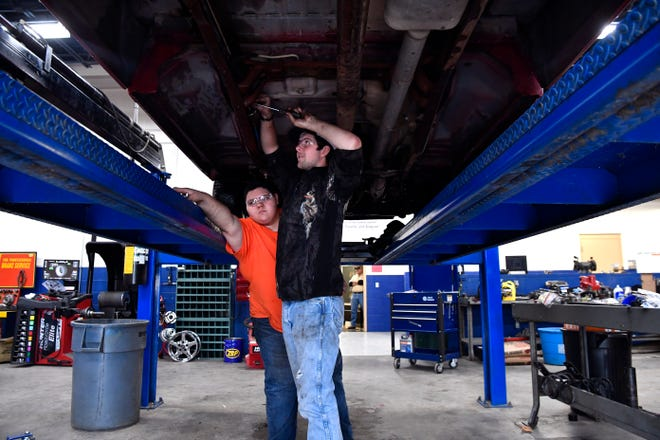 Ethan Elam reaches past Ben Hayes who is changing a fuel filter on a pickup Tuesday in a Cisco College automotive technology class in Abilene.