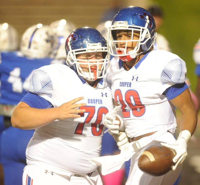 Cooper center Thomas Squyres, left, celebrates with Aeneas Favors after Favor's scored on an 11-yard touchdown run on the game's opening drive. The Cougars went on to beat Amarillo Palo Duro 49-15 last week.