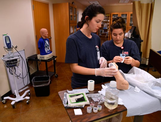 Nursing students Katelin Reyes (left) and Bryhana Welch practice wound care on a mannequin foot Tuesday at Cisco College in Abilene.