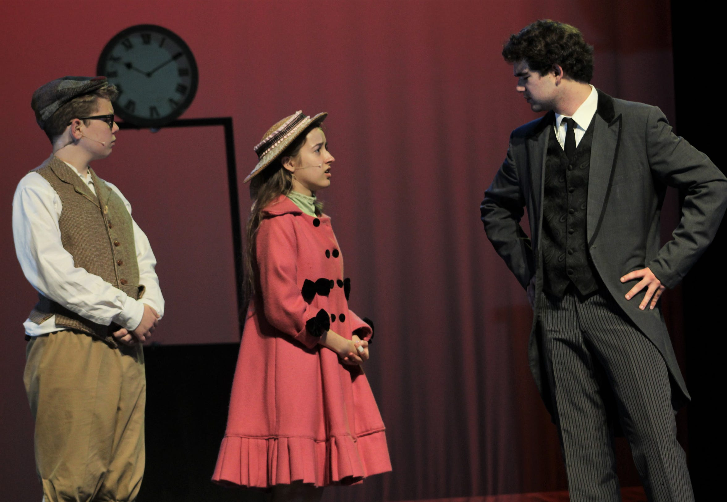 """George Banks (Josh Shuler), at his bank, disapproves of his children Michael (Case Kirby) and Jane (Kyla Sutton) showing up unannounced in this rehearsal scene from """"Mary Poppin,"""" Wylie High's fall musical."""