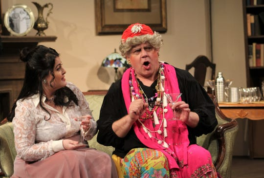 """Madame Arcati (Mike Stephens) regales her hosts, including Violet Bradman (Eva Luna-Wheeler), upon her arrival and first drink at the Condomine home for a seance in this rehearsal scene from """"Blithe Spirit,"""" Abilene Community Theatre's second show of the 2018-19 season."""