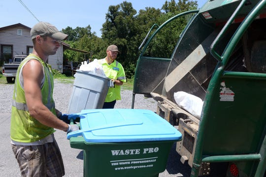 Waste Pro workers load trash into a rear-loading garbage trust. Sometimes seals can go bad in these trucks, resulting in trash 'juice' leaking onto roadways. Waste Pro inspects the trucks daily to prevent this from happening, though.