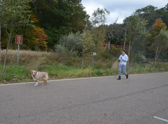 Kaci Sparks of Battle Creek walks her dog, Chief, at Historic Bridge Park on Monday, October 15, 2018.