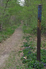 A trail post with directions for the North Country National Scenic Trail and the Calhoun County Trail at Ott Biological Preserve on Arlington Ave. in Battle Creek.