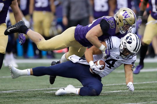 Washington linebacker Ben Burr-Kirven tackles Brigham Young running back Lopini Katoa during a Sept. 29 game in Seattle.