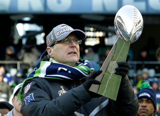Paul Allen lifts the Vince Lombardi trophy during a celebration on Feb. 5, 2014, at CenturyLink Field in Seattle. Allen, billionaire owner of the Portland Trail Blazers and the Seattle Seahawks and Microsoft co-founder, died Monday at age 65.
