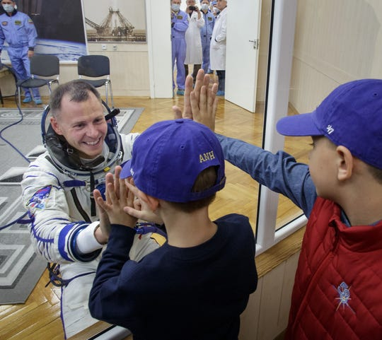 Nick Hague of NASA says farewell to his sons after having his Sokol suit pressure checked ahead of his launch on a Soyuz rocket with Alexey Ovchinin of Roscosmos on Thursday, Oct. 11, 2018 at the Baikonur Cosmodrome in Kazakhstan.