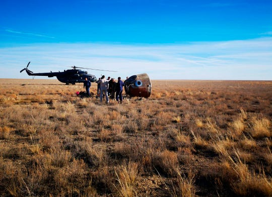 In this photo provided by Russian Defense Ministry Press Service, the rescue team gathered next to the Soyuz MS-10 space capsule after it made an emergency landing in a field about 280 miles northeast of Baikonur, Kazakhstan, on Thursday, Oct. 11, 2018.
