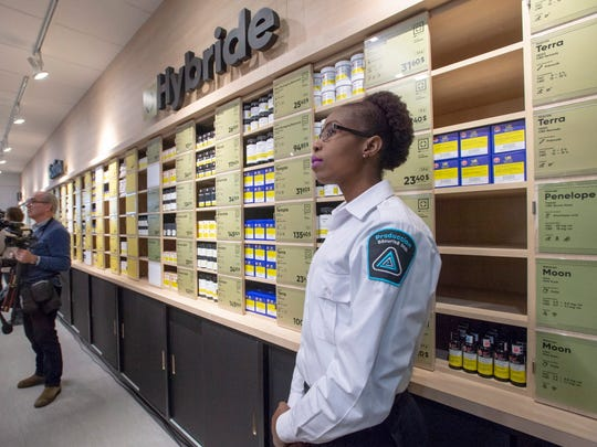 A security guard keeps an eye on reporters and photographers at a new Societe Quebecoise du Cannabis (SQDC) store during a media preview Tuesday, Oct. 16, 2018 in Montreal. The legal sale of cannabis begins in Canada on Wednesday, Oct. 17, 2018. (Ryan Remiorz/The Canadian Press via AP)