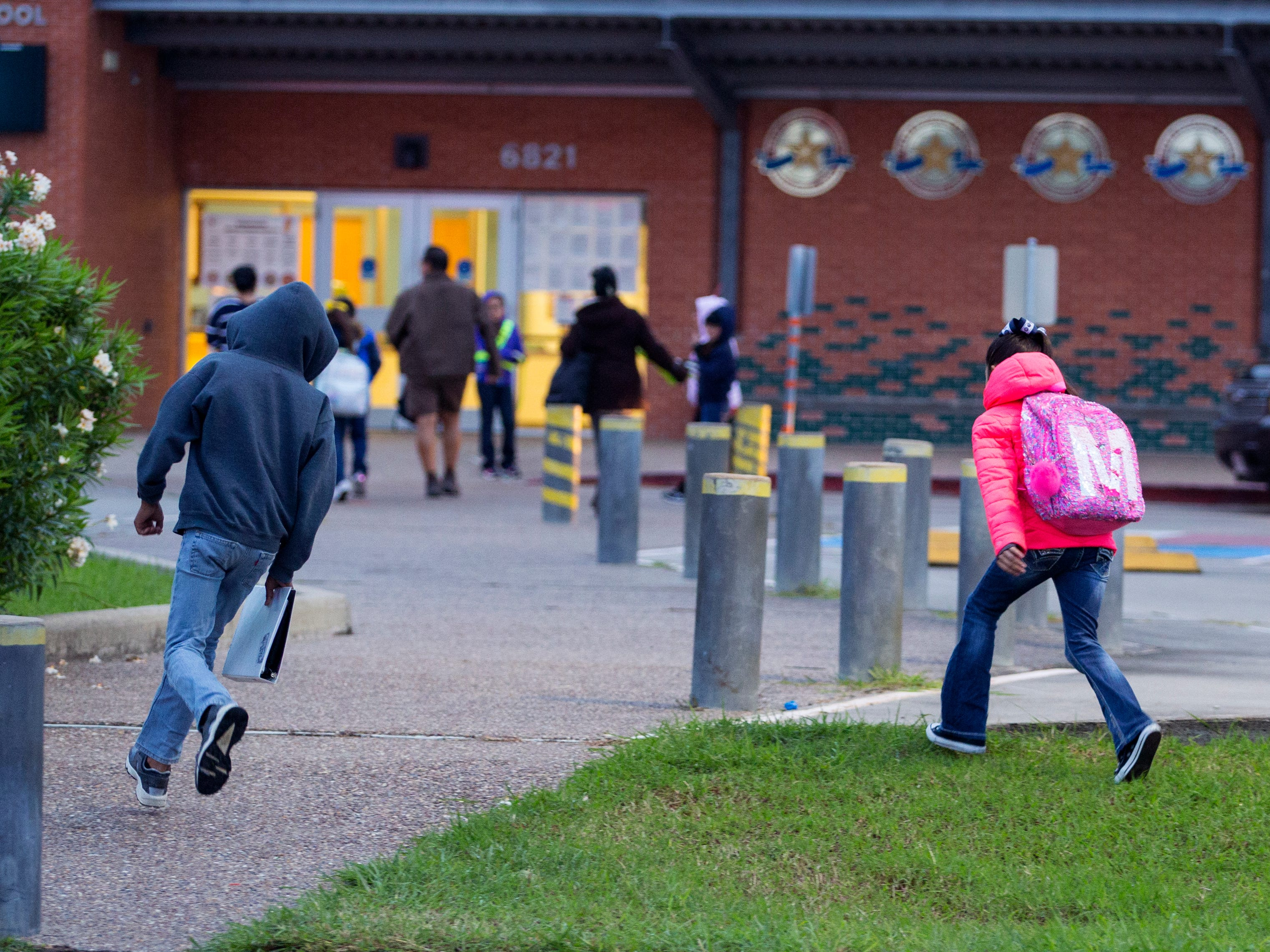 Kids run to school to get out of the cold at Dawson Elementary School on Tuesday, October 16, 2018. The Coastal Bend will continue to see isolated showers and thunderstorms in the early part of the week and get slightly warmer toward the weekend.