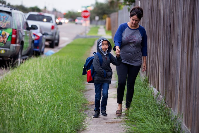 Chance Trevino (left), 5) and Suzan Moore head to school at Dawson Elementary School on Tuesday, October 16, 2018. The Coastal Bend will continue to see isolated showers and thunderstorms in the early part of the week and get slightly warmer toward the weekend.