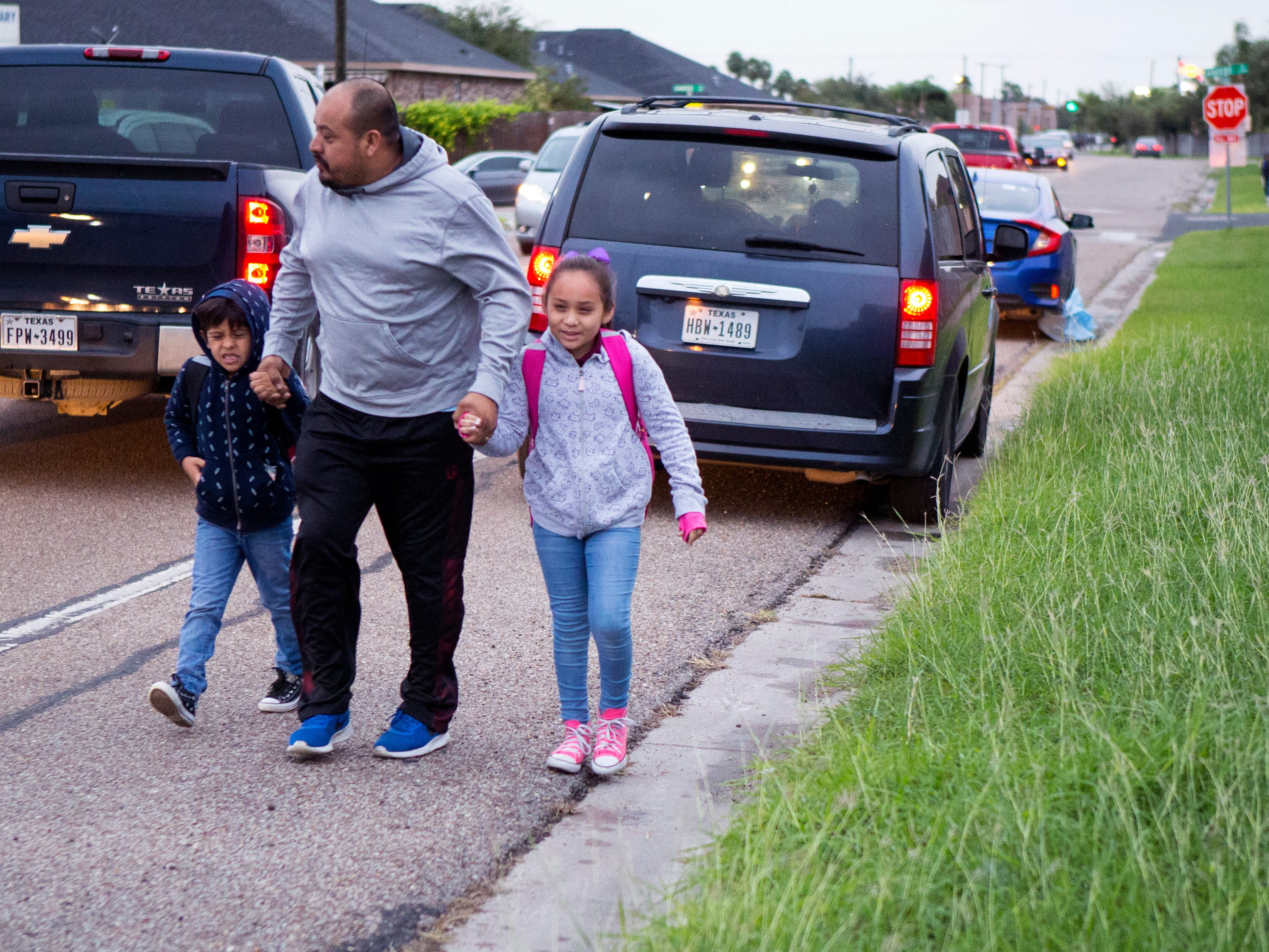 Edgar Alaniz Jr. (from left), 7, Edgar Alaniz and Alexa Alaniz, 8, head to school at at Dawson Elementary School on Tuesday, October 16, 2018. The Coastal Bend will continue to see isolated showers and thunderstorms in the early part of the week and get slightly warmer toward the weekend.