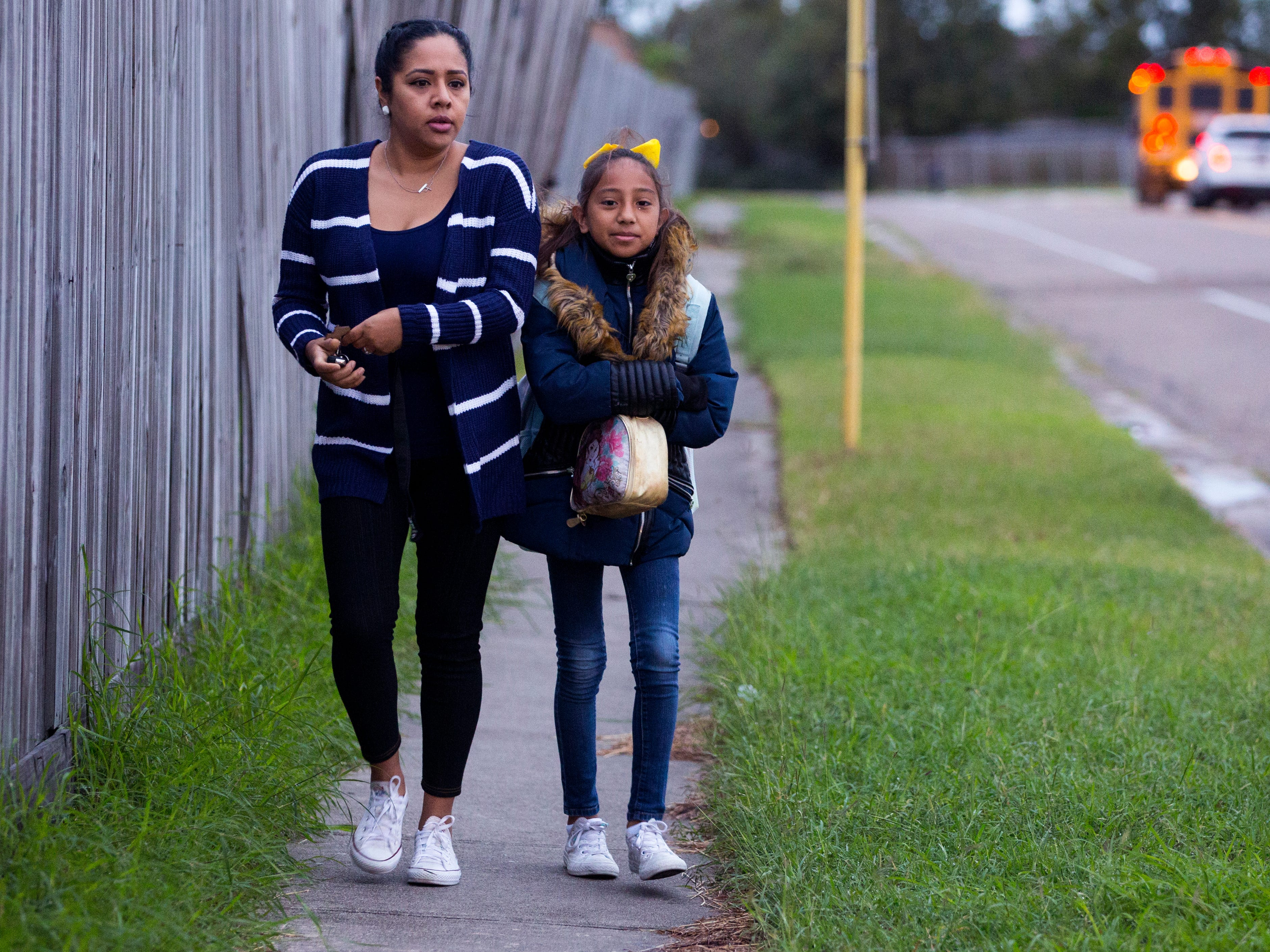 Roxy Torres (left) and Dezirae Cueva, 10, prepare to cross the street as they head to school at Dawson Elementary School on Tuesday, October 16, 2018. The Coastal Bend will continue to see isolated showers and thunderstorms in the early part of the week and get slightly warmer toward the weekend.