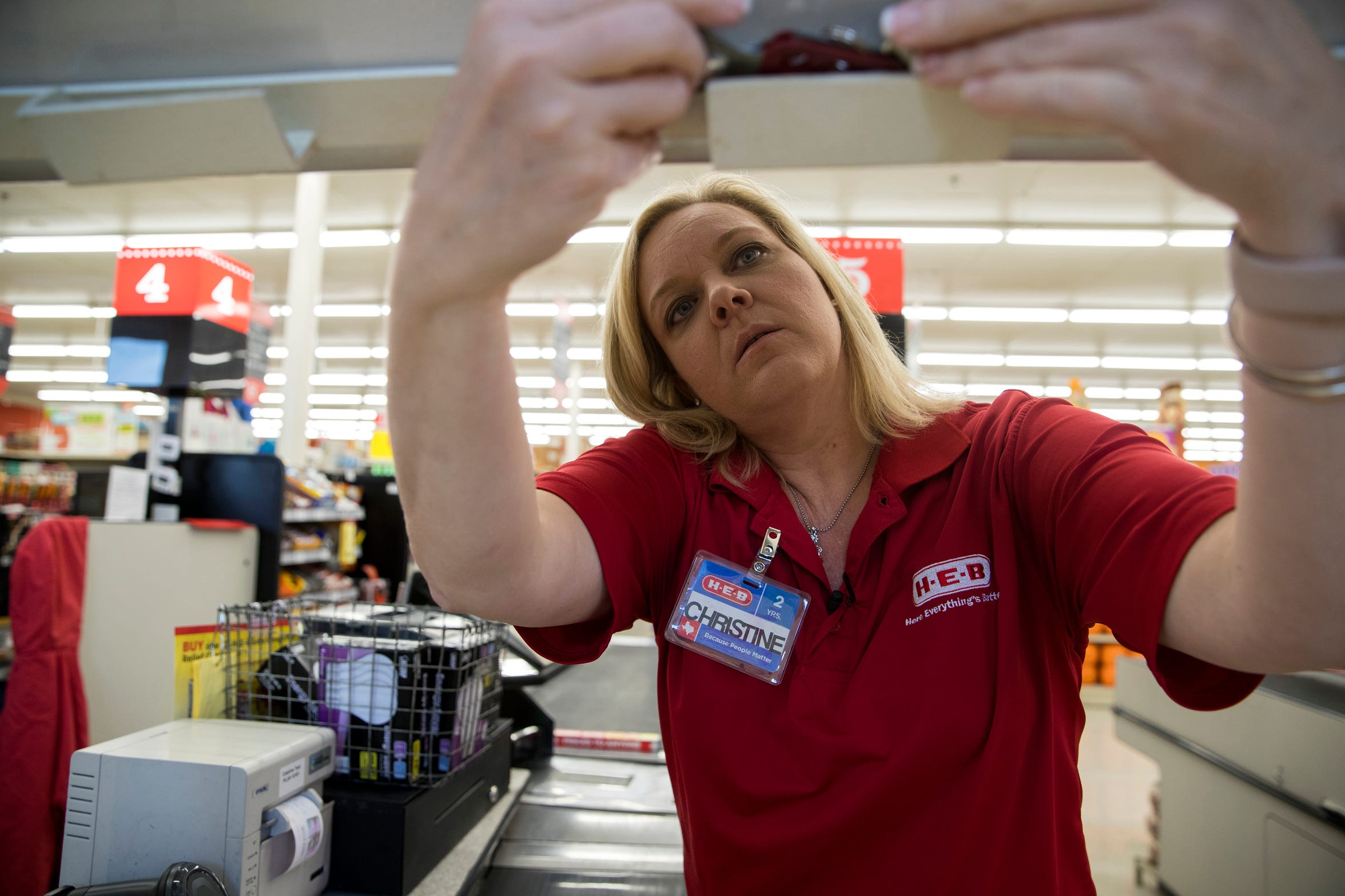"""Christine Kidd McFarland, a fifth-grade teacher at Sinton Elementary School in Sinton, Texas, rubs her neck as she waits for a customer to check out at H-E-B, a grocery store, on Monday, September 17, 2018. Three years ago, she said she applied for free or reduced lunch for her son. """"I'm a teacher. And I qualified for reduced lunch. What does that say?"""""""