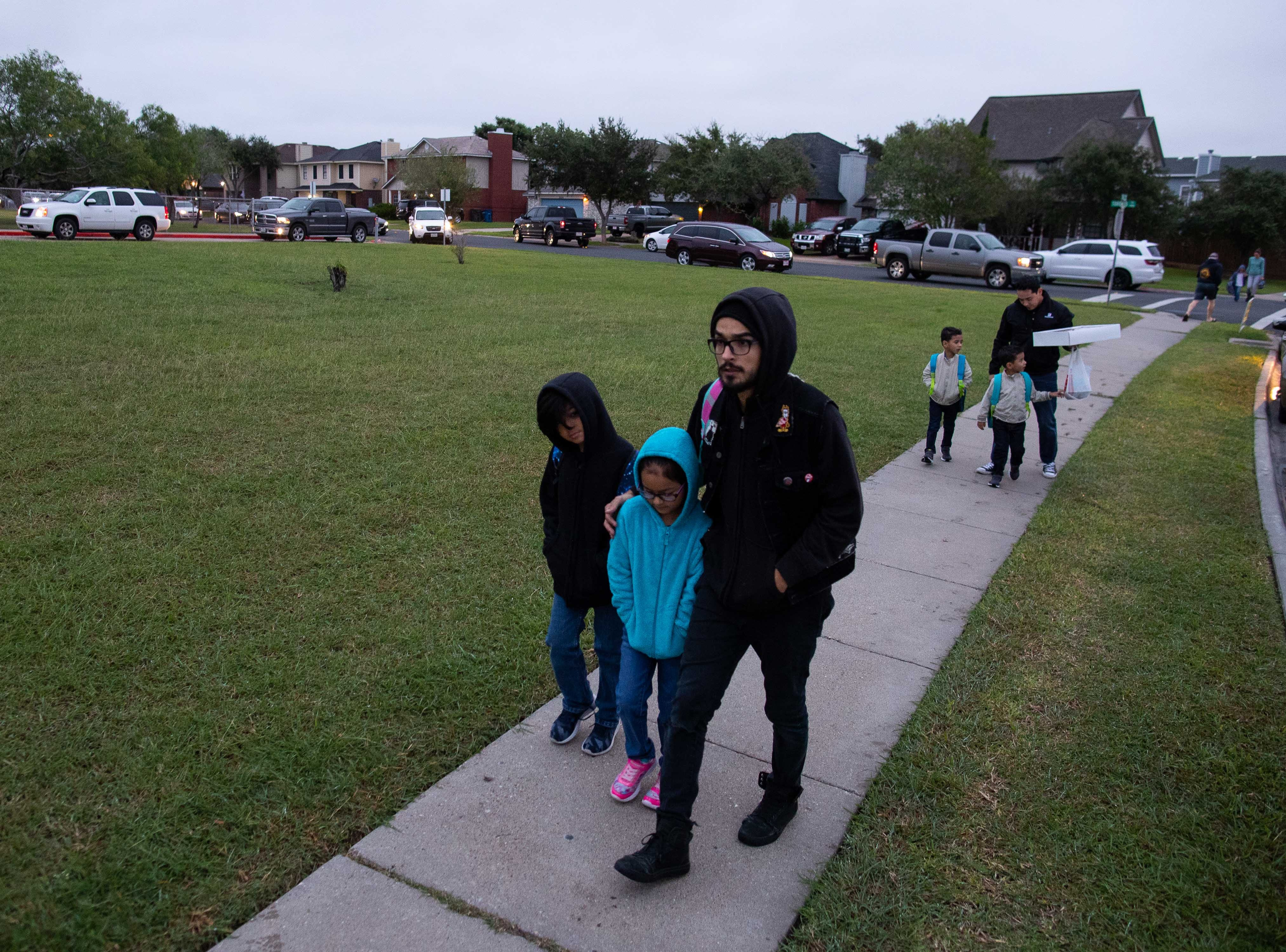 Parents walk their children to school outside Ella Barnes Elementary as temperature drop to the low 50's on Tuesday, Oct. 16, 2018.