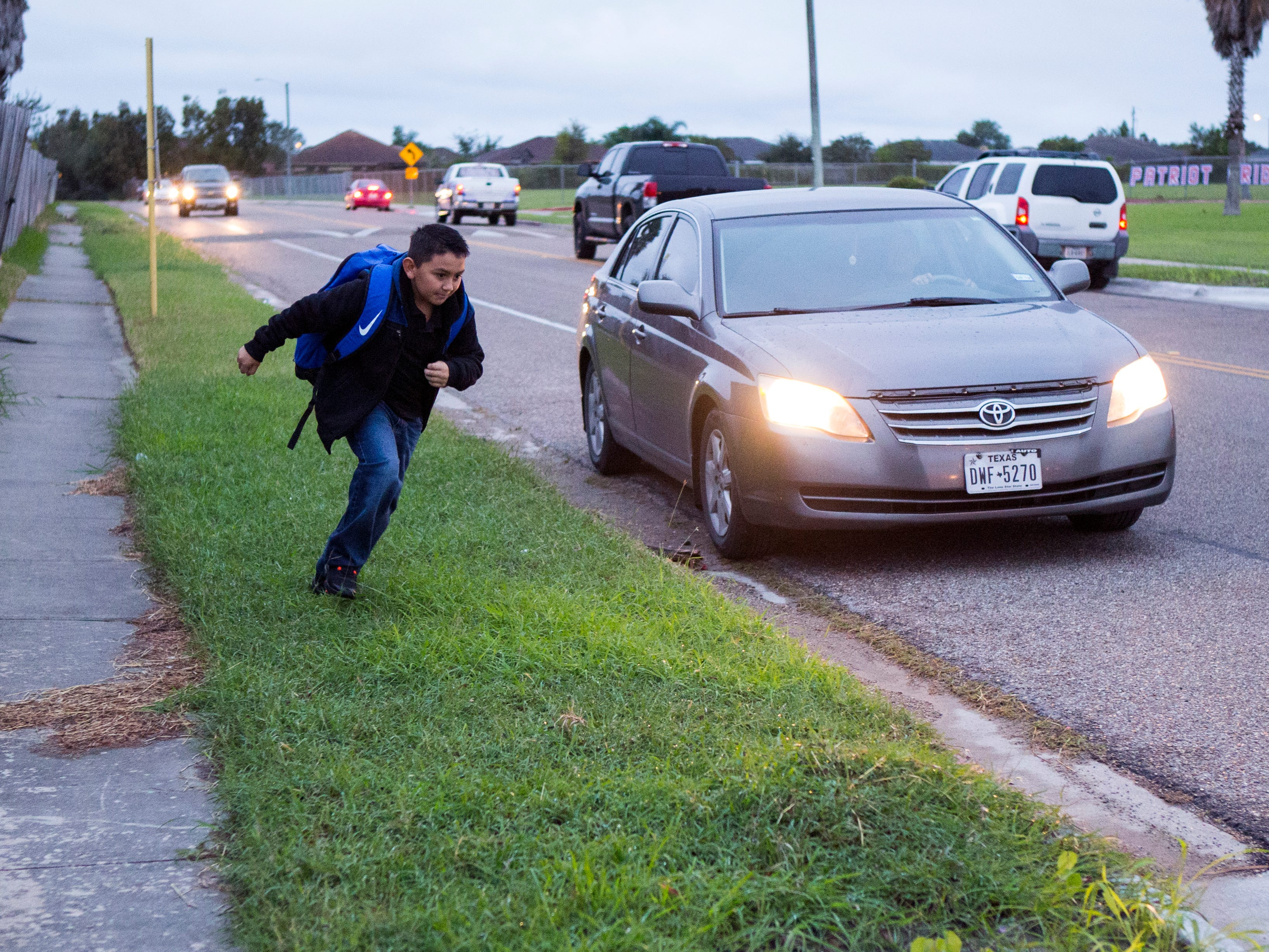 Jonathon Garza, 9, runs across the street to school at Dawson Elementary School to get out of the cold on Tuesday, October 16, 2018. The Coastal Bend will continue to see isolated showers and thunderstorms in the early part of the week and get slightly warmer toward the weekend.
