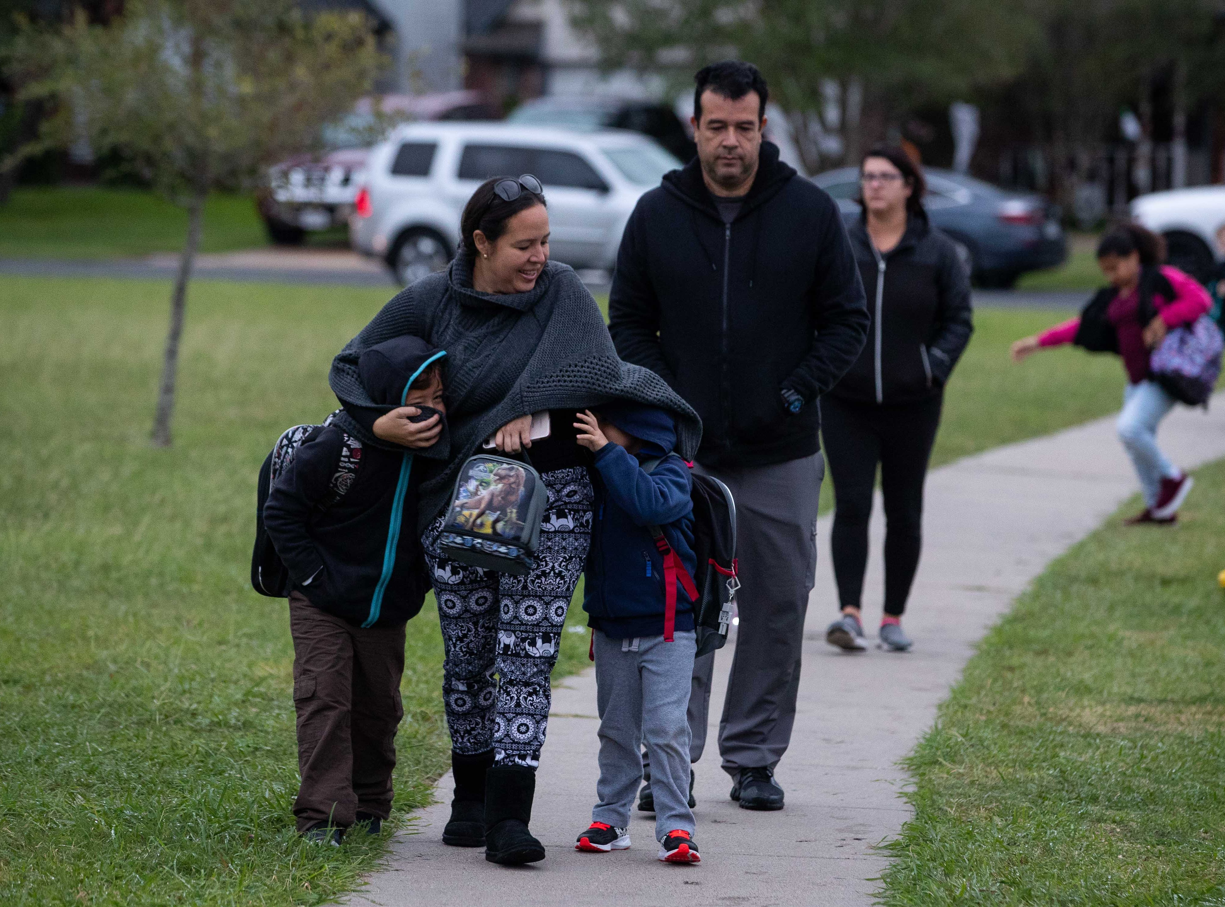 Two children say warm next to their mother as they walk to Ella Barnes Elementary as temperature drop to the low 50's on Tuesday, Oct. 16, 2018.