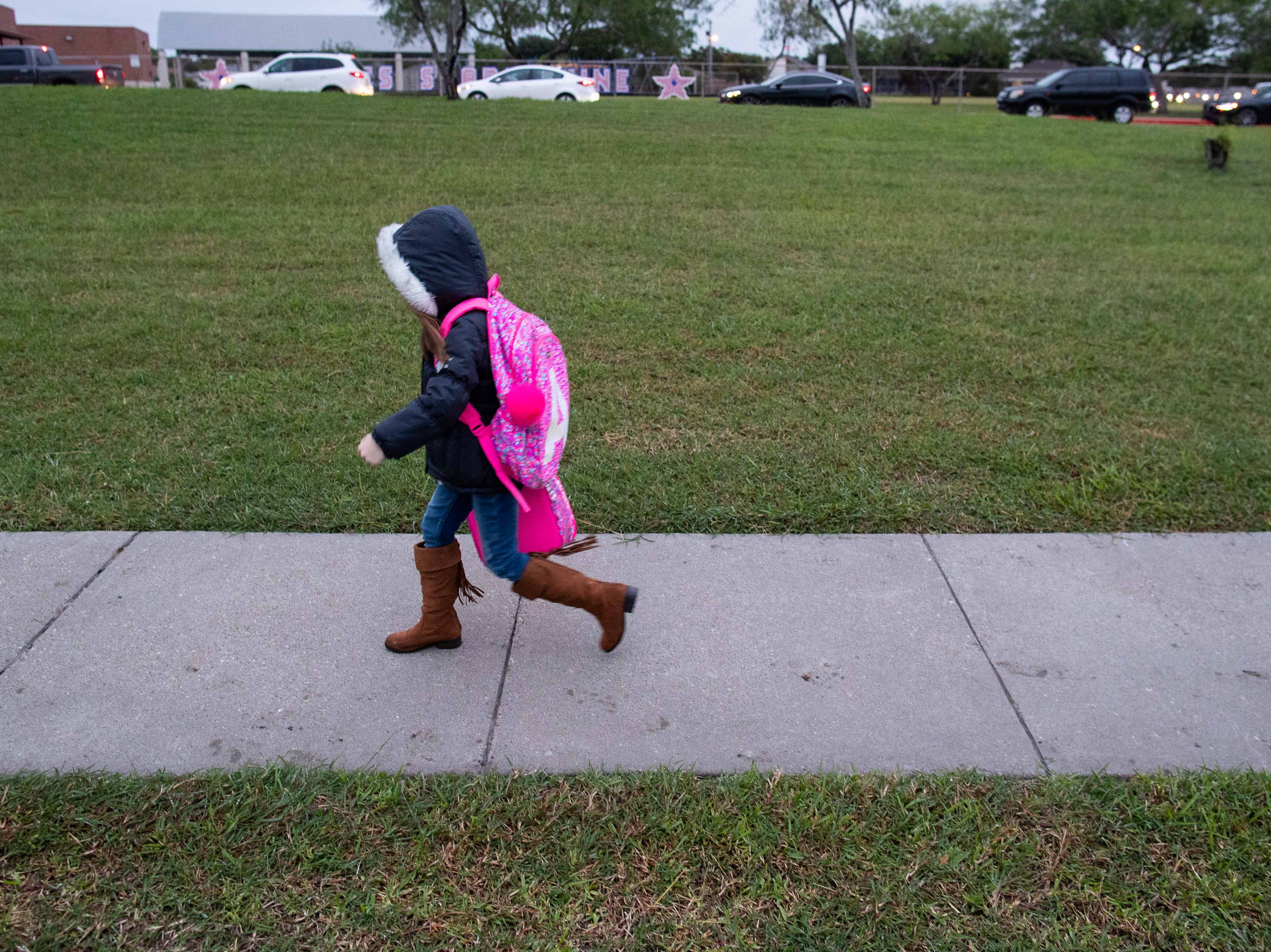 A young kid dressed in a jacket walks to Ella Barnes Elementary as temperature drop to the low 50's on Tuesday, Oct. 16, 2018.
