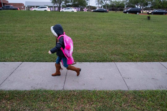 A young kid dressed in a jacket walks to Ella Barnes Elementary on Tuesday, Oct. 16, 2018.
