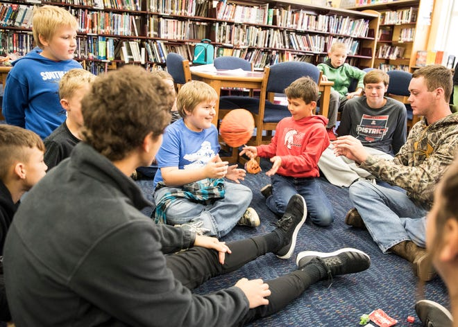 Brendyn Canter-West, third from right, quickly passes a paper pumpkin to a fellow student to avoid being taken out as students play a game of musical pumpkins, similar to musical chairs, where the one with the pumpkin is taken out of the game when the music stops as part of the Big Brothers, Big Sisters partnership at Southeastern High School.