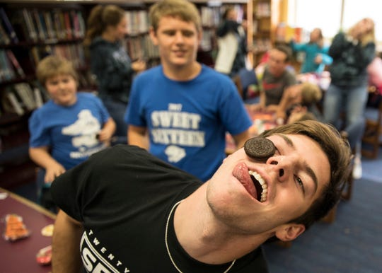 "Southeastern senior Lucas Meininger tries to get an Oreo cookie from his forehead to his mouth as others watch during a game at Southeastern High School as part of the Big Brothers, Big Sisters partnership in Chillicothe, Ohio, Tuesday morning. ""I think it is great program that gives us time to mentor kids who may not have the home life we do,"" said Meininger."
