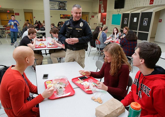 This Feb .14, 2018 photo shows Northwest School District School Resource Officer Dennis Muntean talking with students, Olivia Wyles, left to right, Cora Jandecka, and Ian Yoder during their lunch period at Northwest High School on Canal Fulton, Ohio.