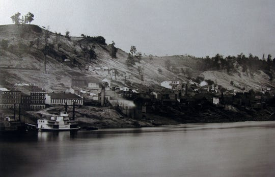 """Daguerreotype of the Cincinnati skyline taken by photographers Fontayne & Porter in the fall of 1848 from Newport, Kentucky. To the left above an unnamed steamboat is the building """"Passenger Depot Little Miami Railroad."""" It just commenced train service three weeks prior to the picture being taken and made a trip form Cincinnati to New York possible for the first time in an optimistic 71 hours. The building at center is the first pumping station for the Cincinnati Water Works."""