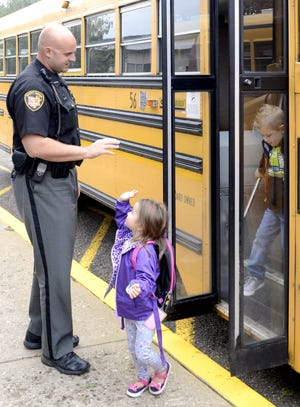 This April 2018 photo shows Stark County Sheriff's Department Deputy Chad Smith giving a high five to Ainsley Marcum at Middlebranch Elementary School in Canton, Ohio. As schools around the country grapple with how to fund security improvements and mental health services, some Ohio districts are hoping to raise millions of dollars by banding together to put the issue before voters this November, while others are making a ballot push independently.