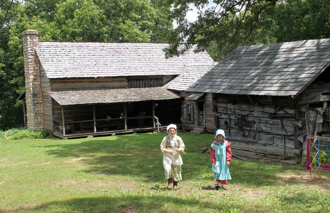Girls dressed in period attire make their way across the grounds of Historic Collinsville.
