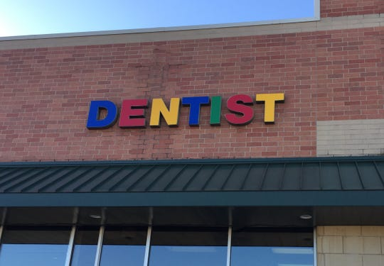 The sign outside the West Des Moines office of dentist Phelan Thomas, in a strip mall at 4100 University Ave.