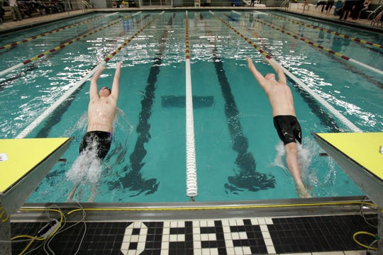 Jack Scafuri, 12, of Waukee, left, and Alek Martin, 13, of Ankeny, take off at the start of the 50 backstroke at the Ankeny YMCA in 2011.