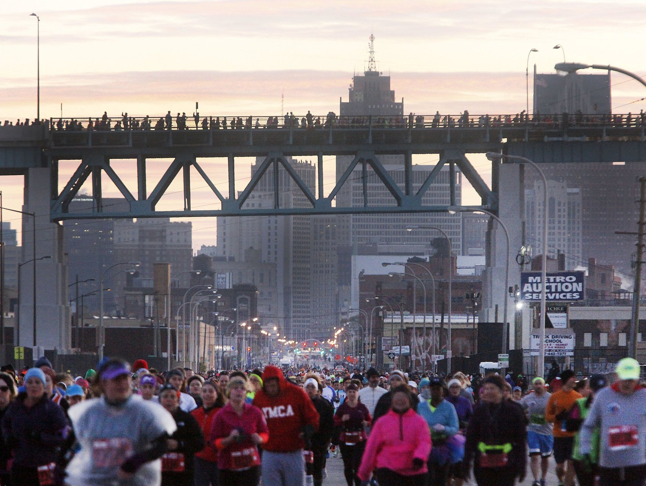 Racers run down Fort Street as other runners cross the Ambassador Bridge during  the 37th Annual Detroit Free Press/Talmer Bank Marathon in Detroit on Sunday, Oct. 19, 2014.