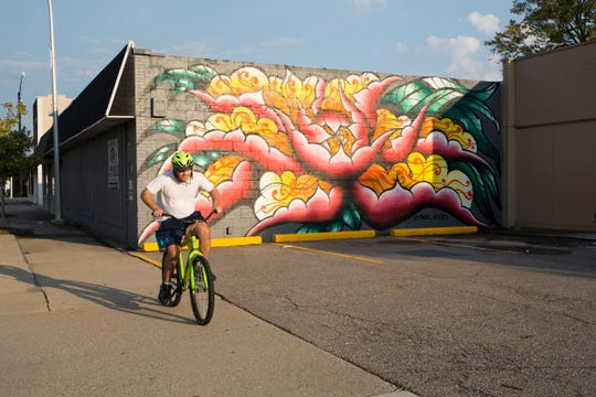 A cyclist passes a mural painted on West 12 Mile in Berkley. Photographed on Monday, Oct 8, 2018.