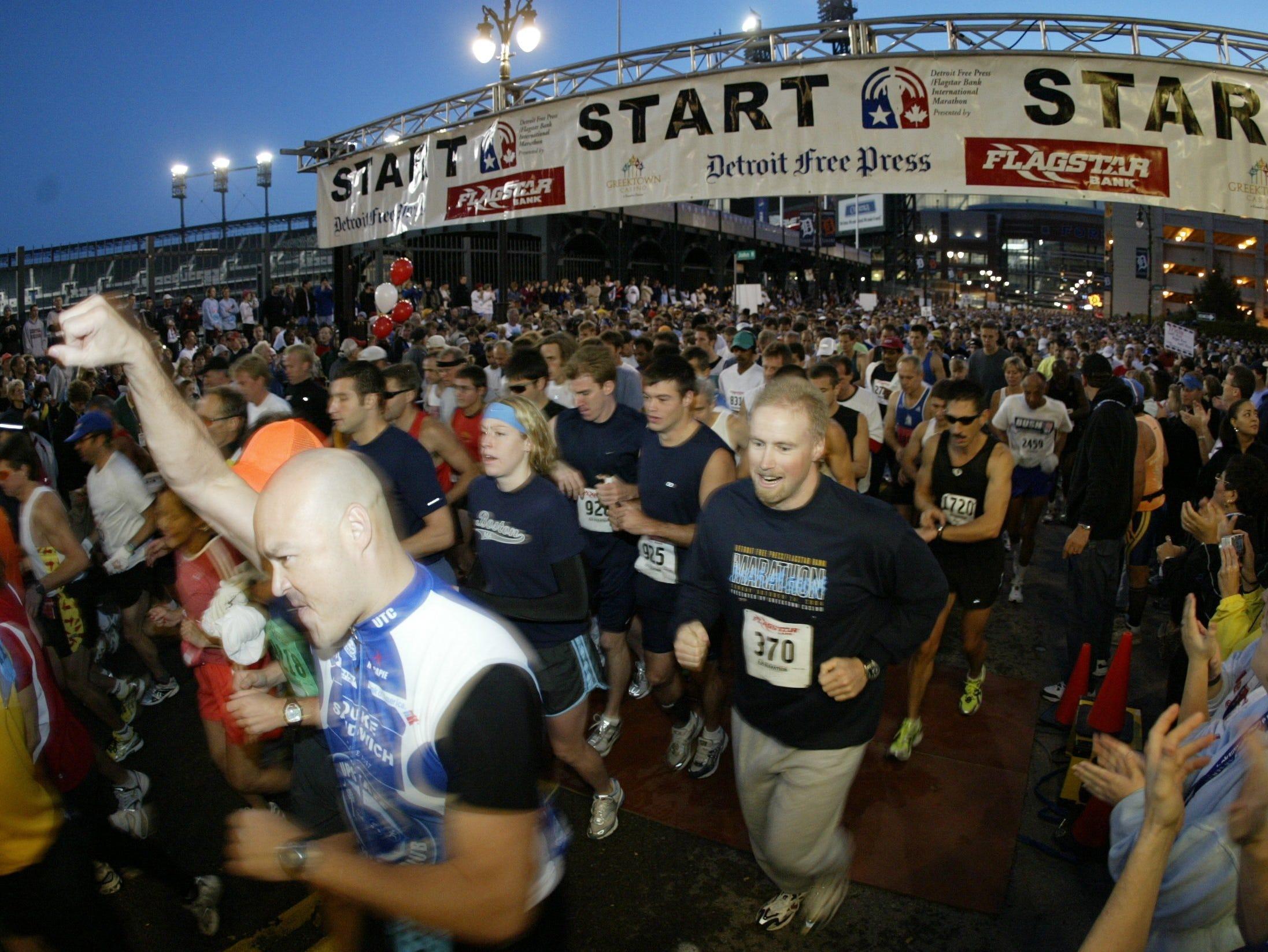 Marathoners, half marathoners and relay teams members run under the start banner next Comerica Park at the start of the 27th annual Detroit Free Press Marathon, Sunday, October 24, 2004 in Detroit, MI.