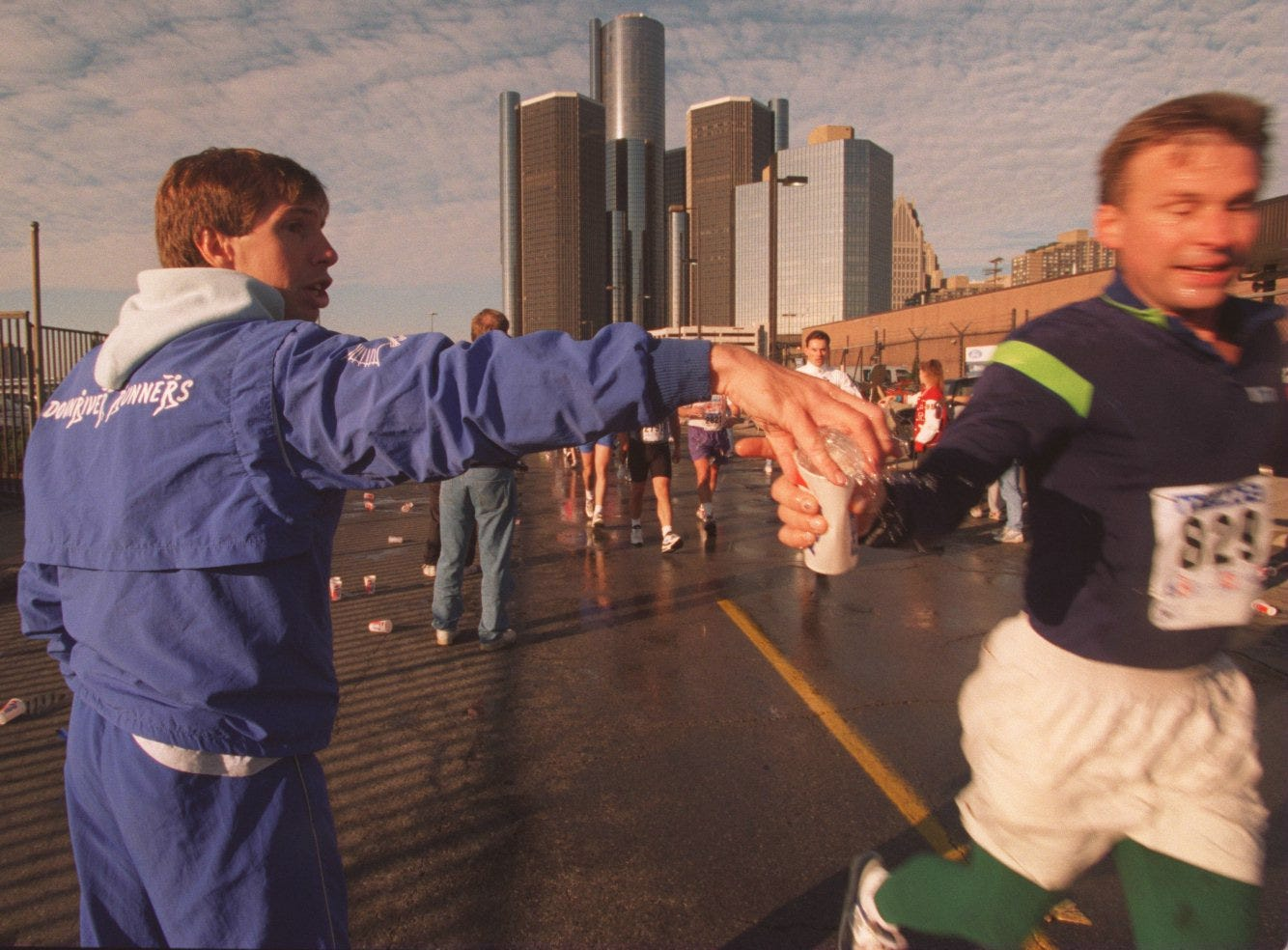Ken Pastor, left of Allen Park, MI,  hands out water to runners at the Ten Mile mark of the Free Press Marathon with the Ren Cen in the background.