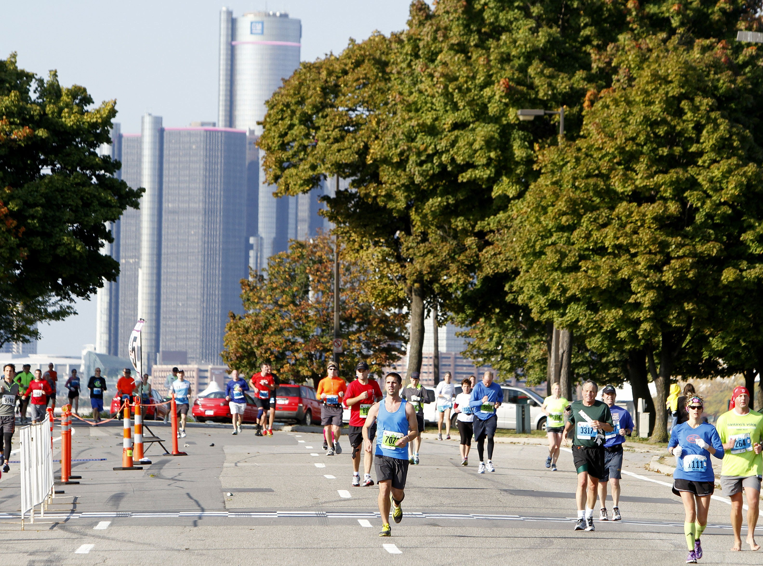 Runners make their way around Belle Isle with the Renaissance Center in the background during the 36th Annual Detroit Free Press/Talmer Bank Marathon in Detroit on Sunday, Oct. 20, 2013.