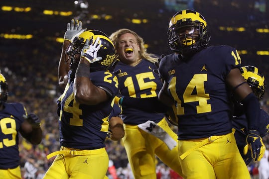 Michigan's Lavert Hill, left, celebrates his touchdown with Josh Metellus (14) and Chase Winovich (15) against Wisconsin on Oct. 13, 2018 at Michigan Stadium in Ann Arbor.