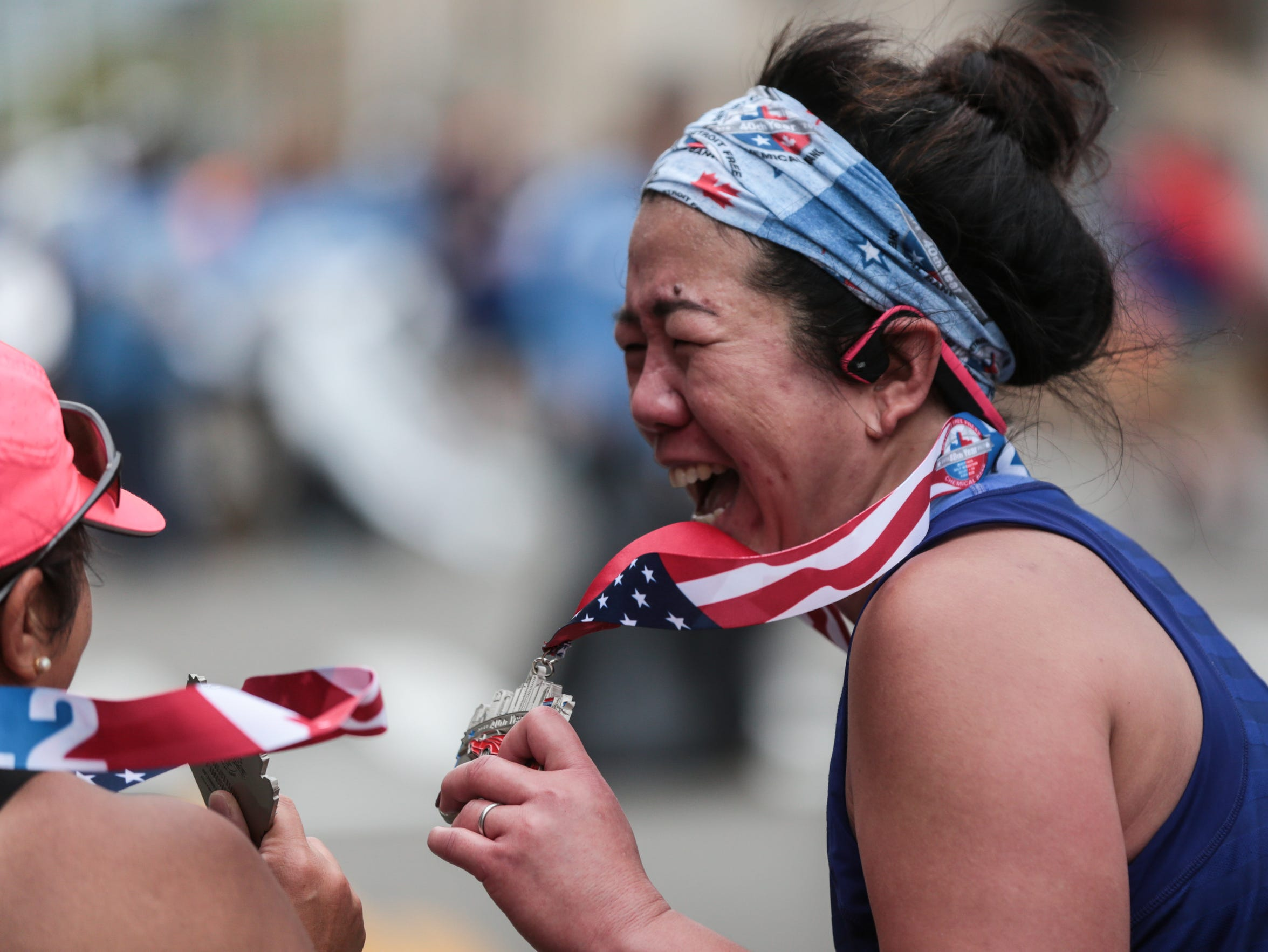 Pauline Lee, right, of Milford and Julia Castillo of Warren show their medals to each other while celebrating finishing the full marathon during the 40th Annual Detroit Free Press/Chemical Bank Marathon in Detroit on Sunday, Oct. 15, 2017.